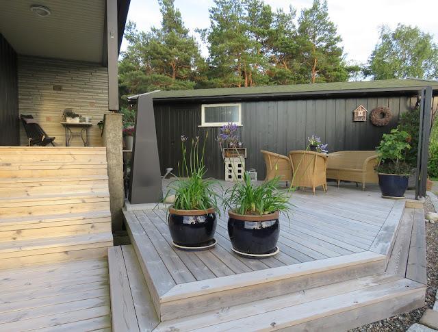 Oversiktsbildet av terrassen med peis og møbler. Furulunden
