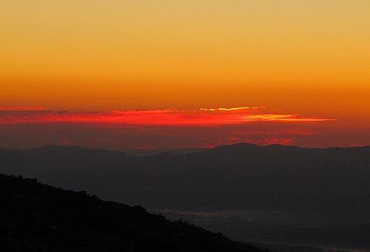 Babia Góra. Intensyfikujące się czerwienie przenoszą się na grupkę obłoków wiszących nad horyzontem.