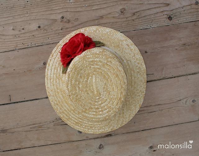 Vista desde el angulo superior del canotier con flores en rojo sobre suelo de madera