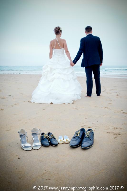 photo mariés sur la plage face à la mer de dos