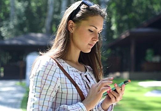 Garota linda usando smartphone ao ar livre