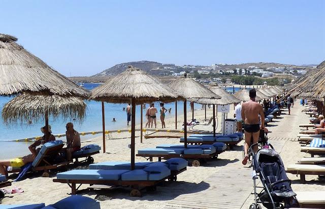 Grecka plaża, Mykonos. Słomiane parasole, niebieskie leżaki, turyści, bezchmurne niebo, błękitne morze.
