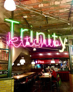 A bright yellow neon sign saying Trinity Kitchen with the kitchen in cursive white font on a bright background.