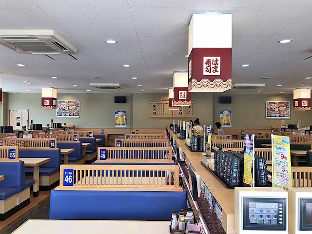 Seating at sushi restaurant, almost empty of customers