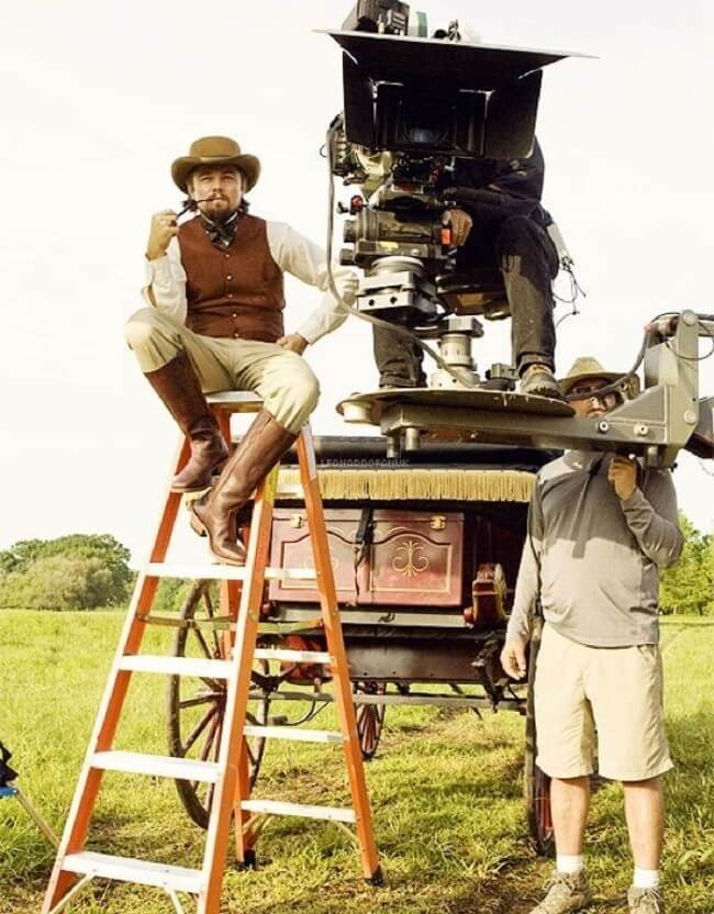 60 Iconic Behind-The-Scenes Pictures Of Actors That Underline The Difference Between Movies And Reality - Leo looks at things from the director's perspective during the shooting of Django Unchained.