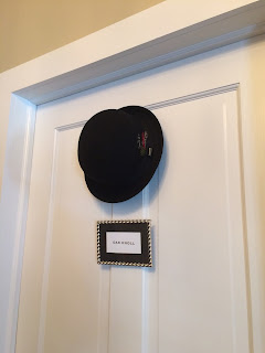 door of bedroom with a bowler hat and a silver frame with room name