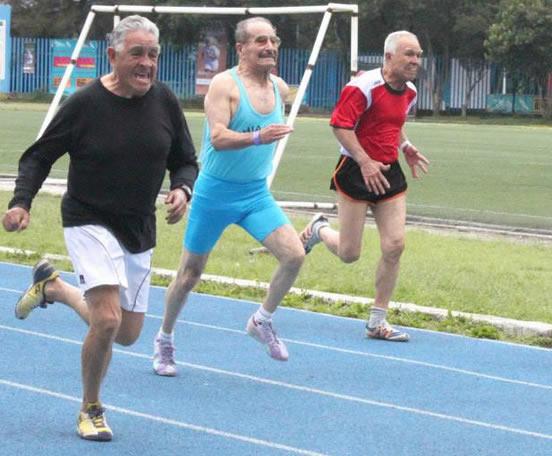 Adultos mayores corriendo en pista atlética.