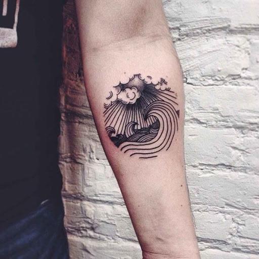 Uma vinheta de o sol brilhando no ondas do mar é retratada em preto e cinza, em que o portador do antebraço neste tatuagem.