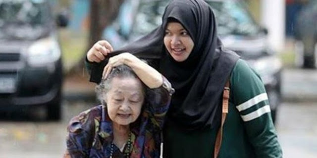 Lindungi Dari Kehujanan, Muslimah Ini Gunakan Kerudungnya Untuk Menutupi Kepala Seorang Nenek