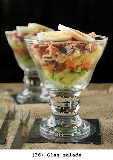 Laagjes salade met aardappel, kaas, eieren, yoghurt, mayonaise, wortel, walnoten, sla en tonijn