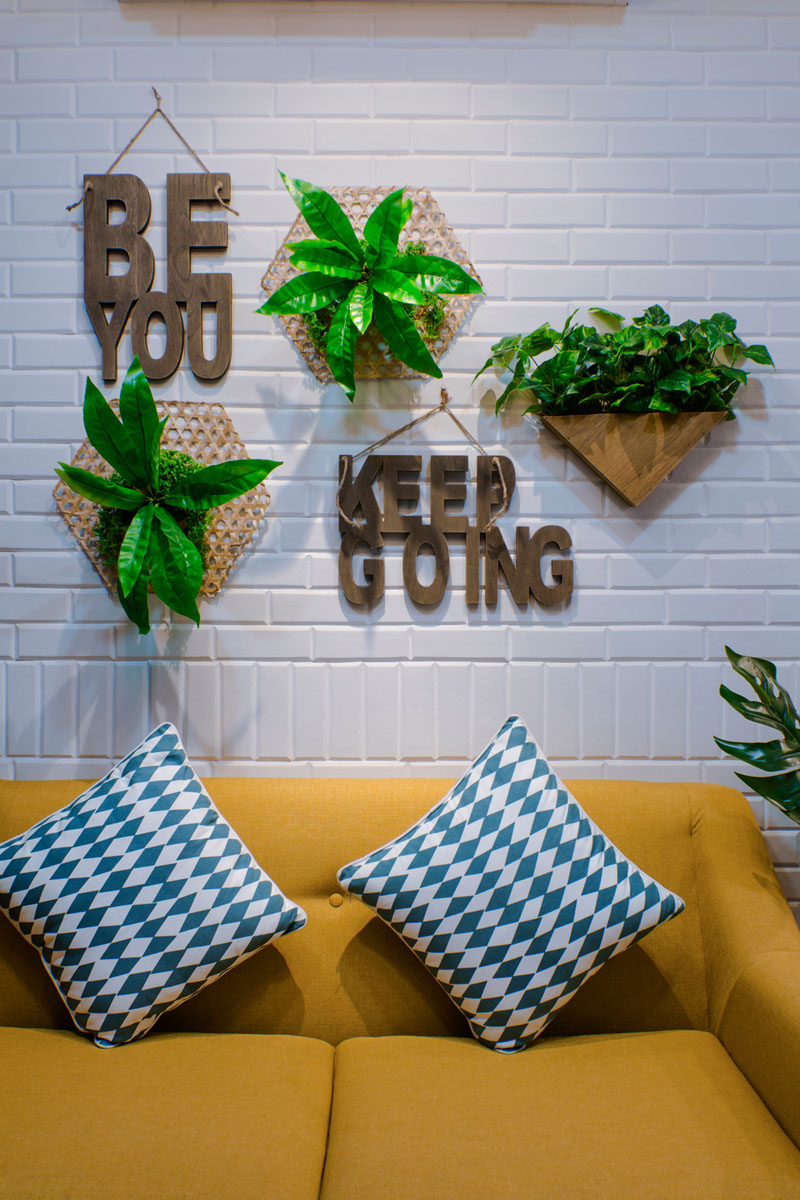 yellow-couch-white-brick-wall-wall-plants-020518-1253-06 Fantastic Blue And Yellow Decorating Ideas Keep This Small Apartment Fun And Bright Interior