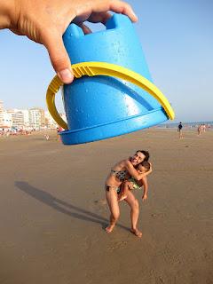 Foto en perspectiva un cubo de playa cubriendo a una mamá con su hijo