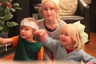 Children in wonder with their Christmas cracker hats.