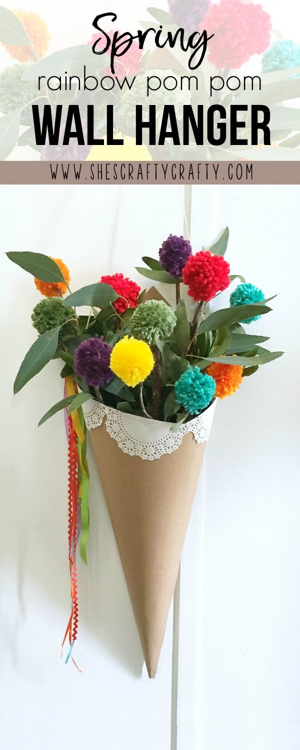 Freshen up your space for Spring with a colorful wall hanging - rainbow pom poms in a cone floral hanger