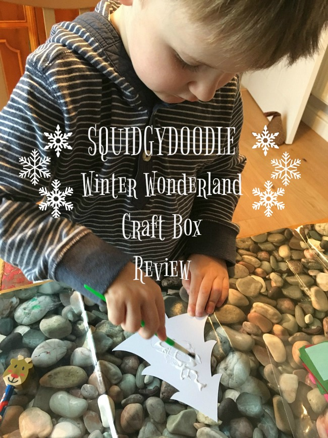 Squidgydoodle-Winter-Wonderland-Craft-Box-Review-text-over-image-of-toddler-applying-glue-to-paper-cut-out-christmas-tree