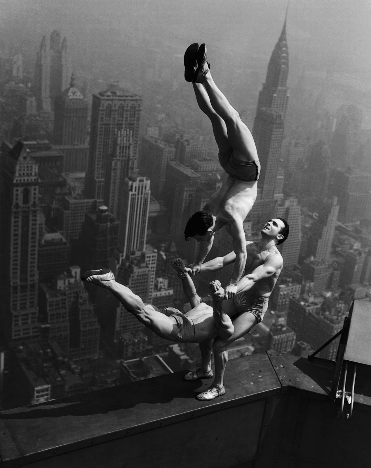 Acrobats balance on top of the Empire State Building, 1934