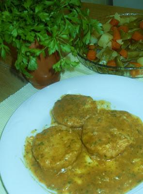 Plato con medallones de merluza cubiertos con salsa verde