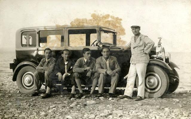 Junge Männer vor uralten Autos