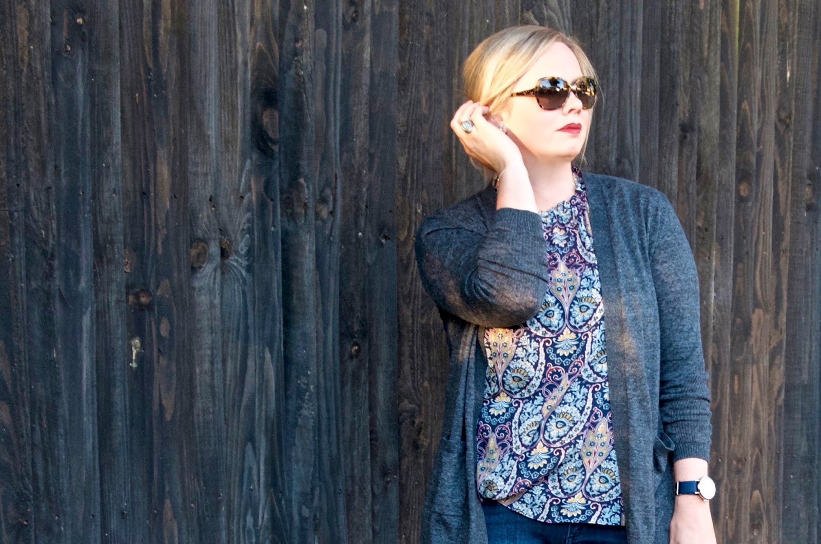 paisley sheer ruffle top with tortoiseshell sunglasses, grey cardigan, jeans and navy grossgrain watch