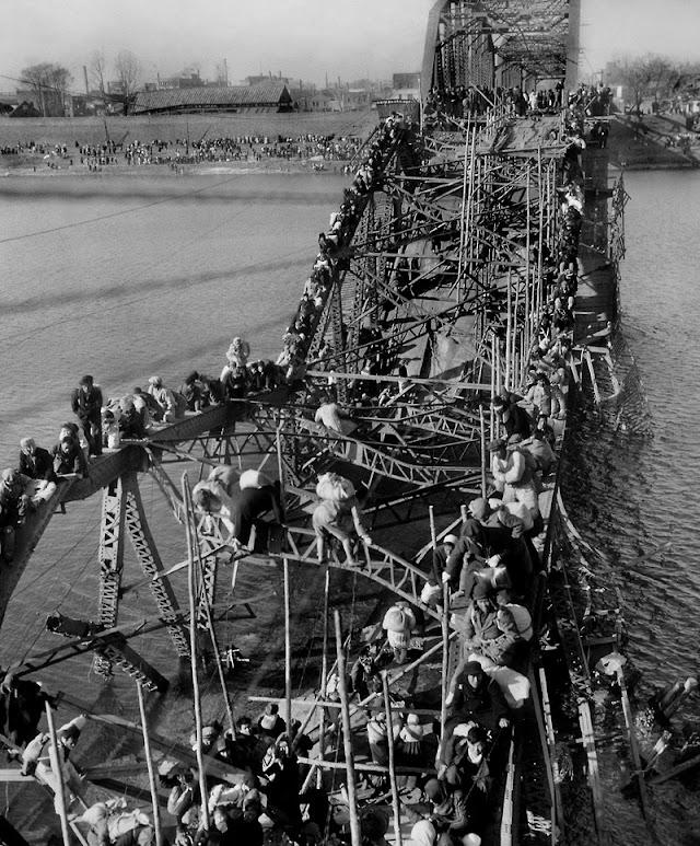 Miles de ciudadanos de Pyongyang evacúan la ciudad a través del semiderruido puente ferroviario sobre el río Daedonggang