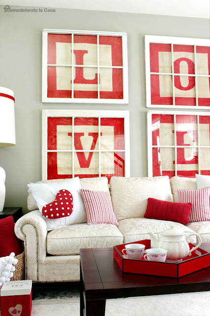 living room dressed for Valentines day with red wall Love art and heart pillow and red tray on coffee table