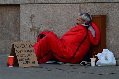 Homeless man in red sleeping bag.