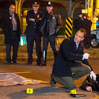 Elementary Sherlock Holmes examining corpse body at a crime scene in CBS Elementary Season 3 Episode 8 End of Watch