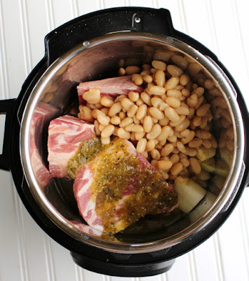 chunks of pork, beans, onions and salsa verde in instant pot ready to cook