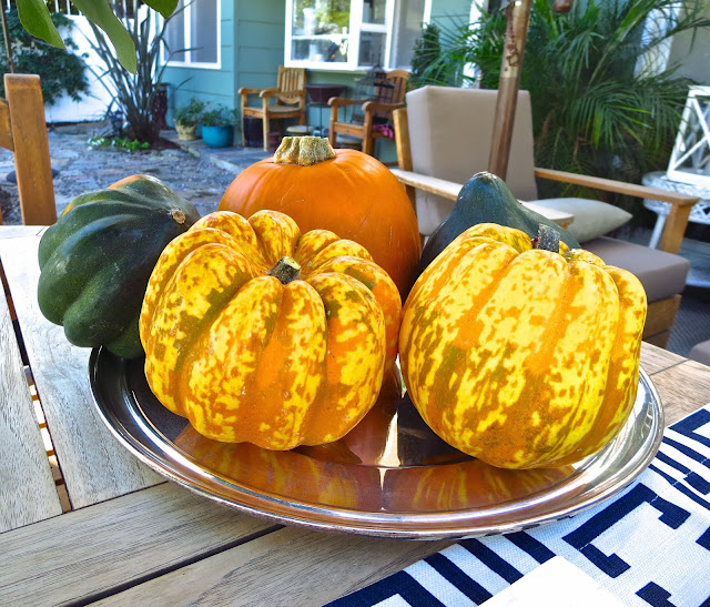 Winter squash on a silver charger at an casual outdoor fall tea