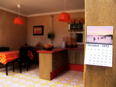 Modern dolls' house miniature 1970s-style kitchen, with a calendar from 1973.