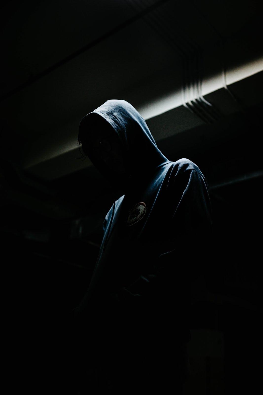رجل غامض يلبس جاكت ازرق في خلفية سوداء