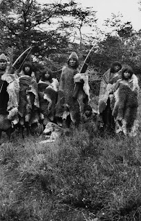 A black and white photograph showing a group of people in furs, holding bows.