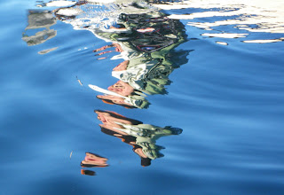 Reflection of canoeist shattered by ripples from bow wake, Nigel Foster