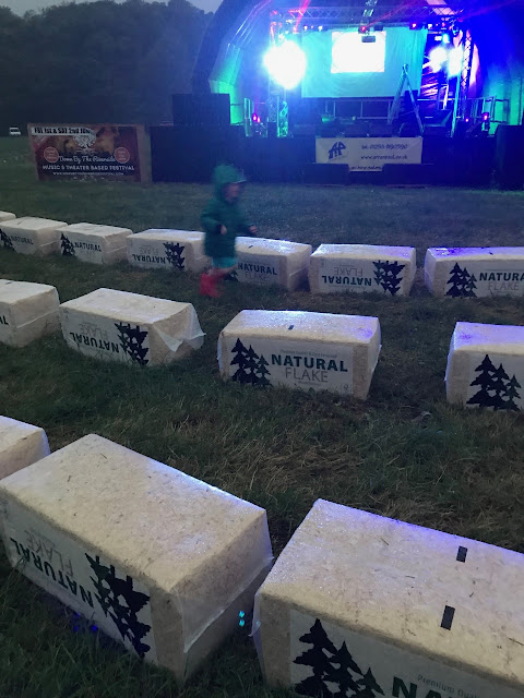 Child jumping on wrapped hay bales in front of a music stage