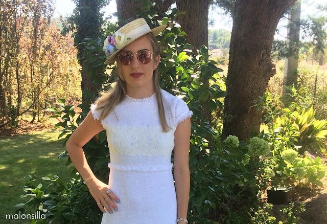 Invitada boda con gafas de sol, sombrero de paja tipo canotier con flores y vestido color claro chanelero