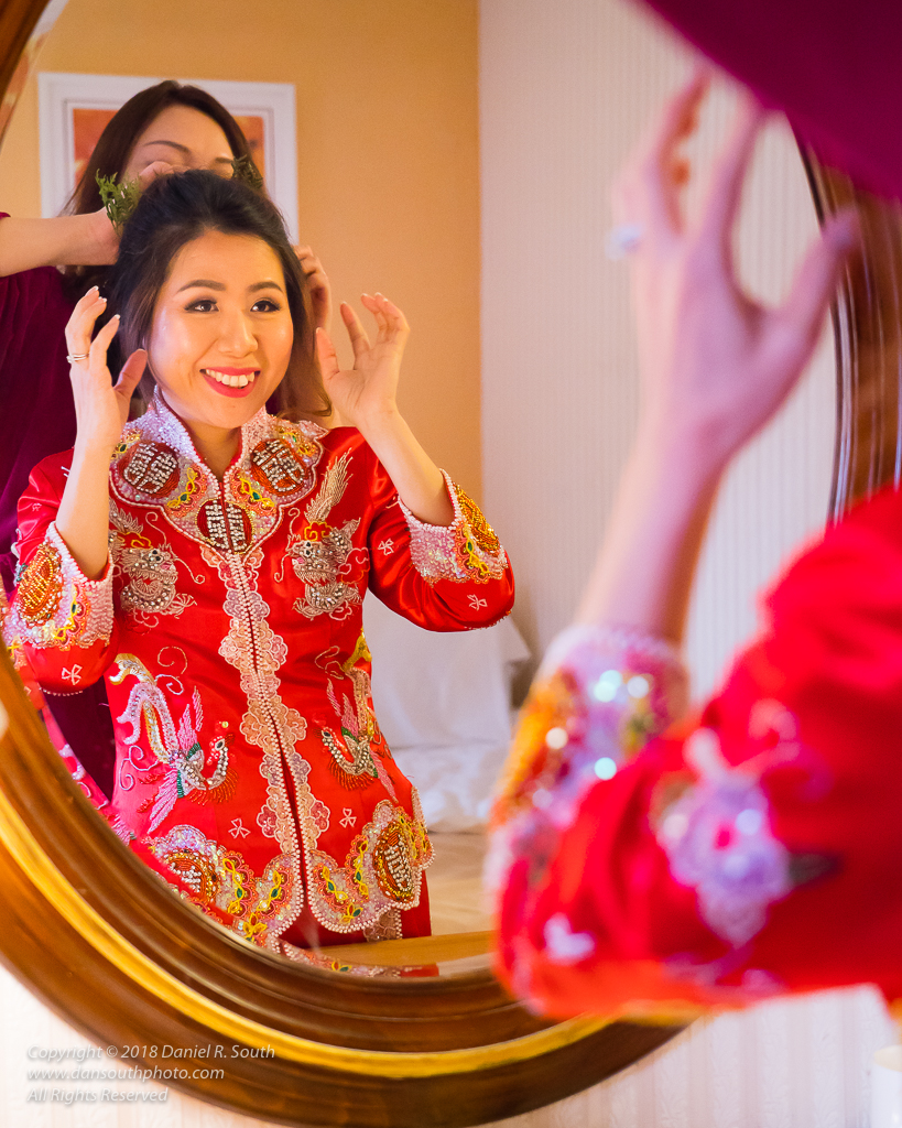 a photo of a bride in a chinese wedding dress checking hair and makeup in a mirror