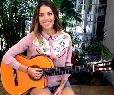 Foto de Debi Nova posando con su guitarra