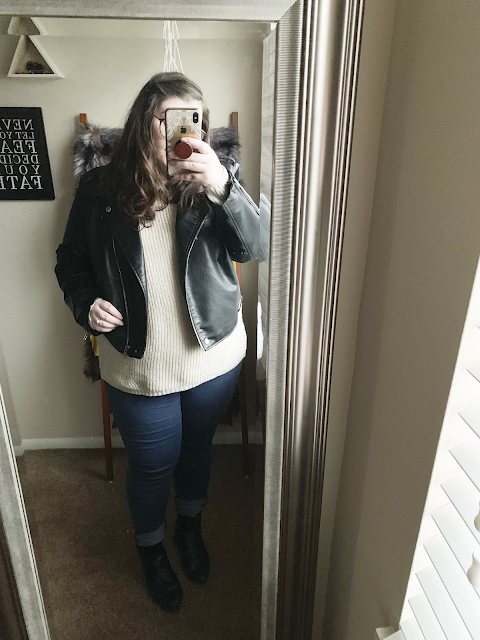 A mirror selfie of an outfit of black faux leather moto jacket, cream sweater, blue skinny jeans, and black heeled chelsea boots..