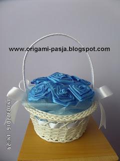 Biały koszyczek z niebieskimi różami ze wstążki.