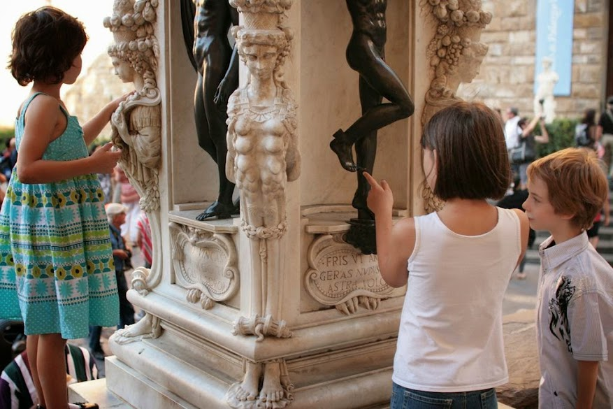Three kids admiring Renaissance sculpture in Florence