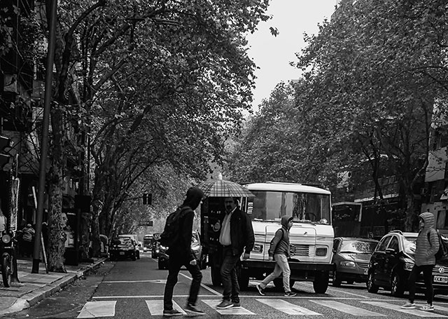 ByN.Gente pasando uno con paraguas mientras garua.