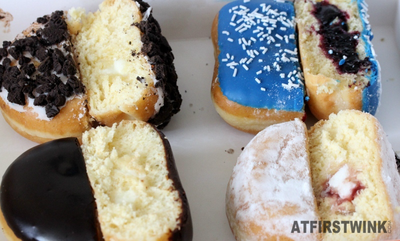 Dunkin Donuts Netherlands White chocolate Oreo, Blueberry Square, Boston creme, and Jelly filled shell cut in half