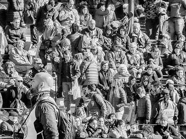 Gente sentada en una tribuna expuesta al sol.