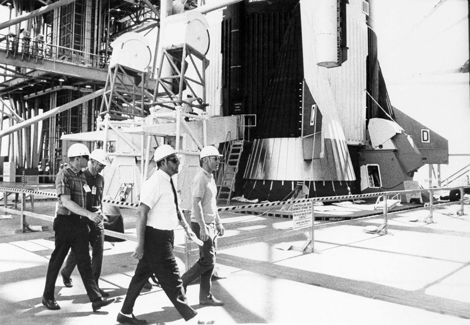 The Apollo 11 crew walks past the base of the massive Saturn V first stage during a walk-through emergency-egress test.