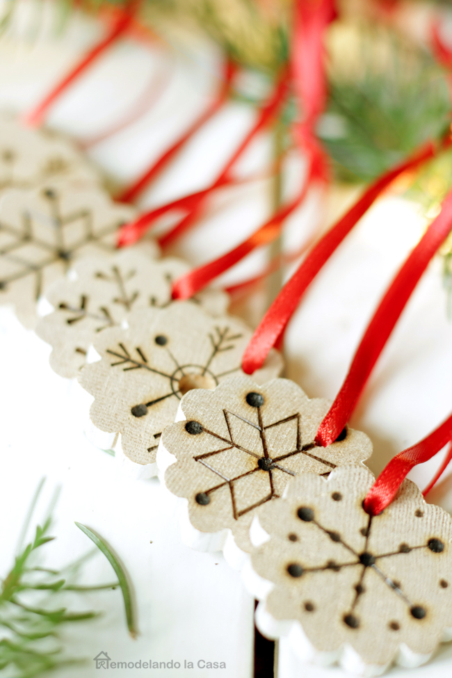 pine branches, red ribbon, wood burning designs