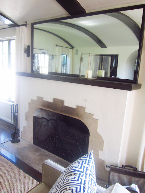 fireplace with Batchelder tiles with two candles and a large mirror on the mantel