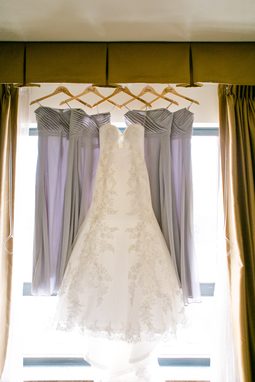 a brideswedding gown and lavender bridesmaid dresses hang in the light of a window