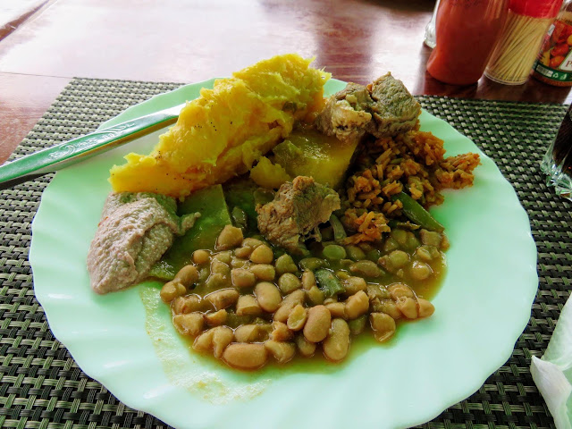 Plate of Ugandan cuisine including matoke and beans