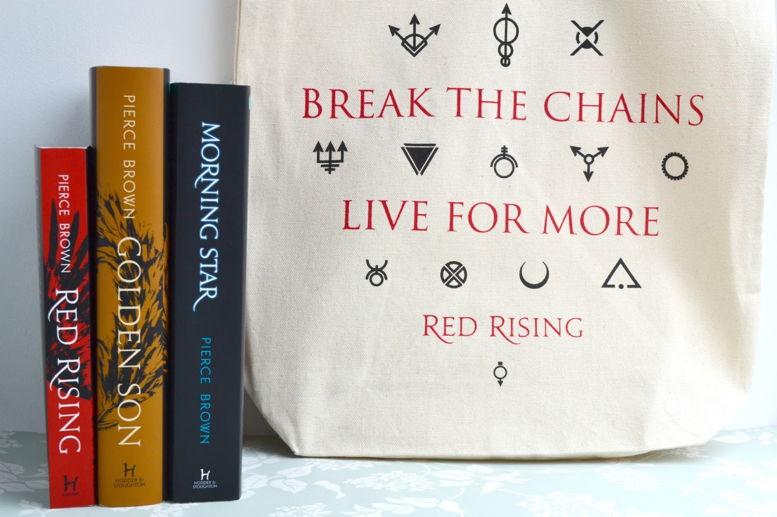 The Red Rising Trilogy by Pierce Brown and a red rising tote bag