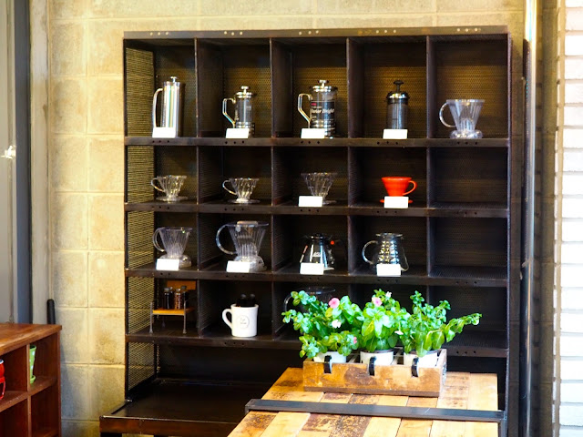 Cafe interior details - shelves of coffee equipment and plants inside Red Velvet Cafe in Myeongnyun, Busan, South Korea